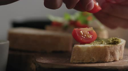 bruschetta : Slow motion closeup man hands making bruschetta with pesto and tomatoes Stock Footage