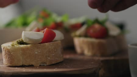 eklemek : Slow motion closeup man hands making bruschetta with pesto, mozzarella and tomatoes Stok Video