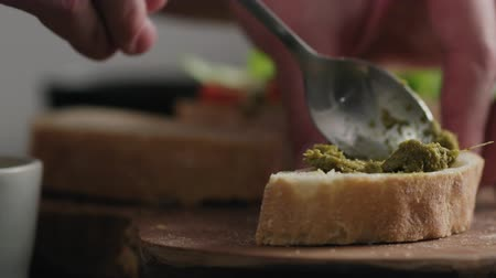 cereal product : Slow motion man spread pesto on ciabatta slice on olive board