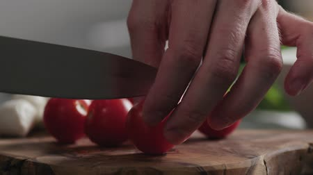 cherry domates : Slow motion closeup man cutting cherry tomatoes on oak board