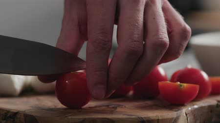 oak : Slow motion closeup man cutting cherry tomatoes on oak board