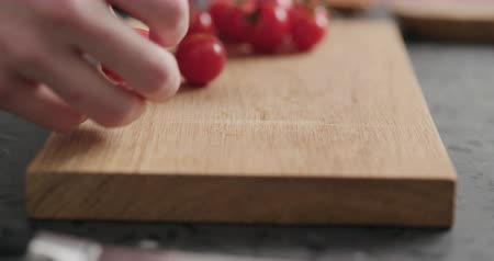 tomate cereja : Man cutting in halves cherry tomatoes on oak wood board