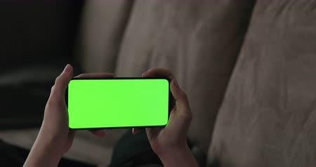 hand gebaar : Young woman lying on a couch and using smartphone with horizontal green screen