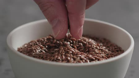 sorteren : Slow motion closeup of man hand takes flaxseed from white bowl Stockvideo