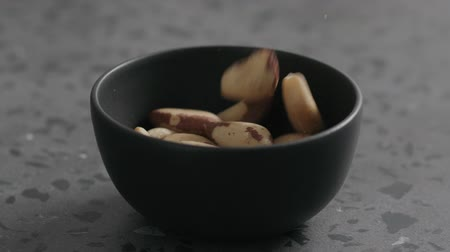 dilis : Slow motion brazil nuts falling into black bowl on terrazzo countertop