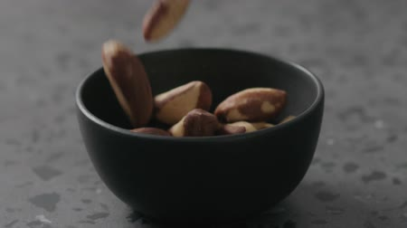 kernels : Slow motion brazil nuts falling into black bowl on terrazzo countertop