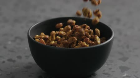 suszone owoce : Slow motion dried seaberry falling into black bowl on terrazzo countertop Wideo