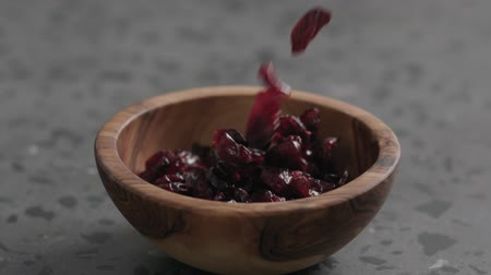 brusinka : Slow motion dried cranberry falling into olive bowl on terrazzo countertop