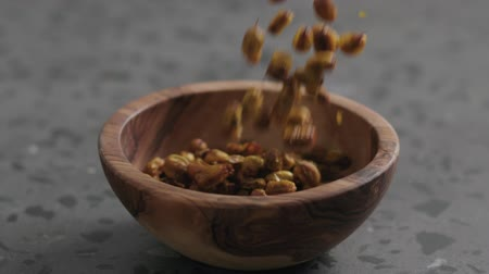 sea buckthorn : Slow motion dried seaberry falling into olive bowl on terrazzo countertop