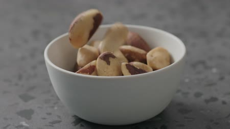 kernels : Slow motion brazil nuts falling into white bowl on terrazzo countertop
