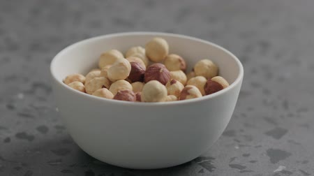 avelã : Slow motion roasted hazelnuts falling into white bowl on terrazzo countertop Stock Footage