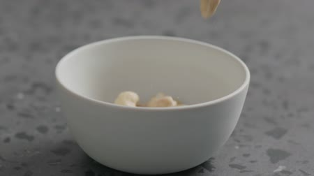 kernels : Slow motion dry cashew falling into white bowl on terrazzo countertop