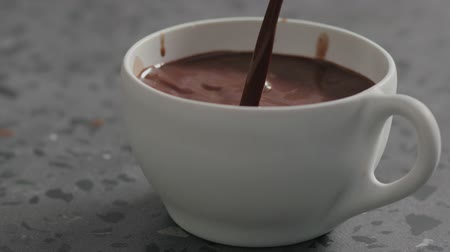 betoniarka : Slow motion pour hot cocoa into white cup on terrazzo countertop