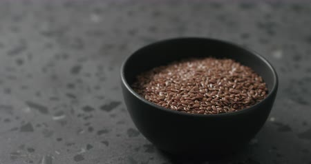 vlaszaad : Slow motion handheld shot of flaxseed in black bowl on terrazzo countertop
