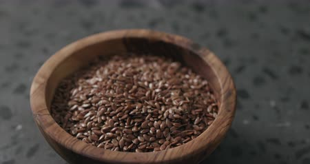 vlaszaad : Slow motion handheld shot of flaxseed in olive bowl on terrazzo countertop