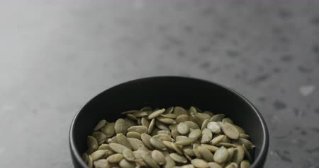 suszone owoce : Slow motion handheld shot of pumpkin in black bowl on terrazzo countertop