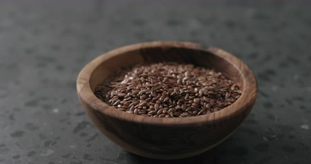 len : Slow motion handheld shot of flaxseed in olive bowl on terrazzo countertop