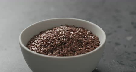 vlaszaad : Slow motion handheld shot of flaxseed in white bowl on terrazzo countertop Stockvideo