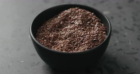 csip : Slow motion closeup of man hand takes flaxseed from black bowl