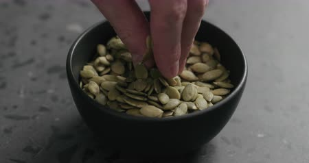 csip : Slow motion closeup of man hand takes pumpkin seeds from black bowl