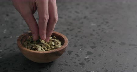 csip : Slow motion closeup of man hand takes pumpkin seeds from olive bowl