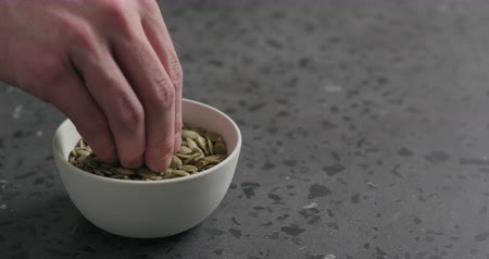 kneifen : Slow motion closeup of man hand takes pumpkin seeds from white bowl