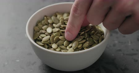csip : Slow motion closeup of man hand takes pumpkin seeds from white bowl
