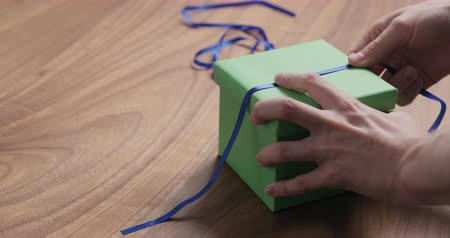nogueira : Slow motion man hand tyingblue ribbon on green paper gift box on walnut table with copy space Vídeos