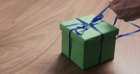 nozes : Slow motion man hand tyingblue ribbon on green paper gift box on walnut table with copy space Stock Footage