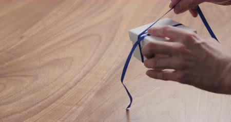 kerstpakket : Slow motion man hand tyingblue ribbon on white paper gift box on walnut table with copy space