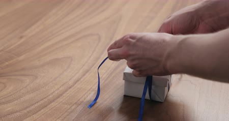 orzech : Slow motion man hand tyingblue ribbon on white paper gift box on walnut table with copy space