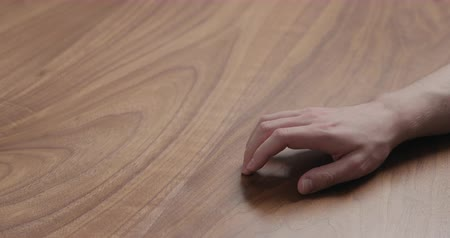 ingressou : Slow motion man hand finger tapping on black walnut table Stock Footage