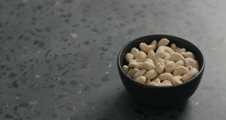 kesudió : Slow motion handheld shot of cashew nuts in black bowl on terrazzo countertop