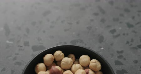 elâ : Slow motion handheld shot of roasted hazelnuts in black bowl on terrazzo countertop Stok Video