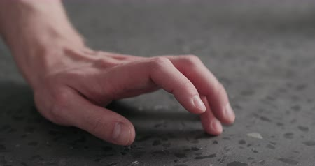 ingressou : Slow motion closeup man finger tapping on terrazzo countertop