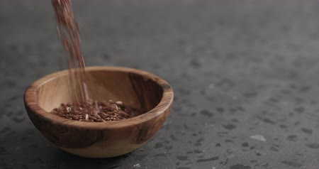 белье : Slow motion flaxseed falling into olive bowl on terrazzo countertop Стоковые видеозаписи