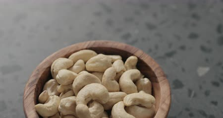 dilis : Slow motion handheld shot of cashew nuts in olive bowl on terrazzo countertop