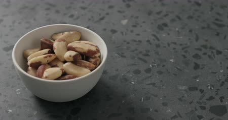 countertop : Slow motion handheld shot of brazil nuts in white bowl on terrazzo countertop