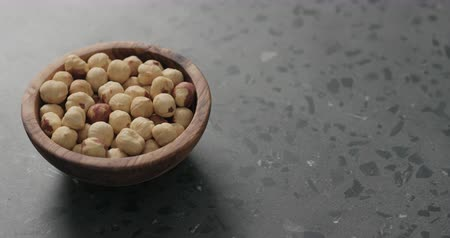 avelã : Slow motion handheld shot of roasted hazelnuts in olive bowl on terrazzo countertop Stock Footage
