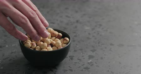 dilis : Slow motion man hand takes hazelnuts from black bowl on terrazzo countertop Stock mozgókép