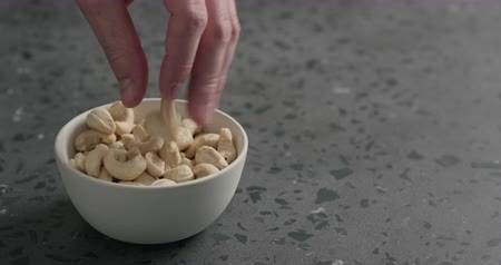 kernels : Slow motion man hand takes cashew nuts from white bowl on terrazzo countertop