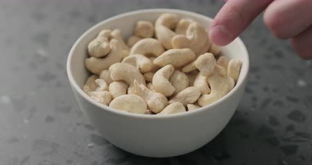 kesudió : Slow motion man hand takes cashew nuts from white bowl on terrazzo countertop