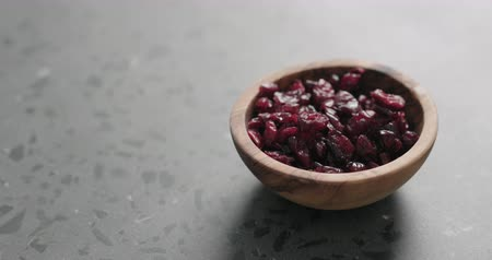 клюква : Slow motion handheld shot of dried cranberry in olive bowl on terrazzo countertop