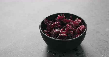 vörösáfonya : Slow motion handheld shot of dried cranberry in black bowl on terrazzo countertop