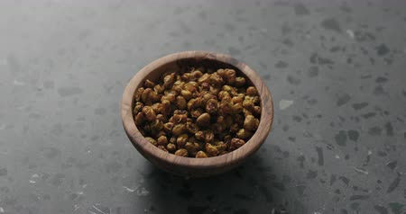 buckthorn : Slow motion handheld shot of dried seaberry in olive bowl on terrazzo countertop