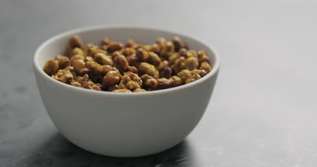 buckthorn : Slow motion handheld shot of dried seaberry in white bowl on terrazzo countertop