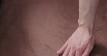 zetel : Slow motion man hand checking brown suede cushion closeup Stockvideo