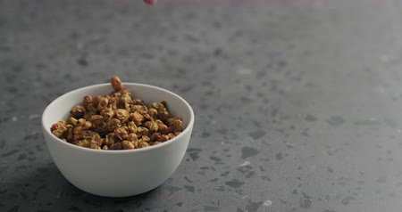 buckthorn : Slow motion man hand take dried seaberry from white bowl on terrazzo countertop