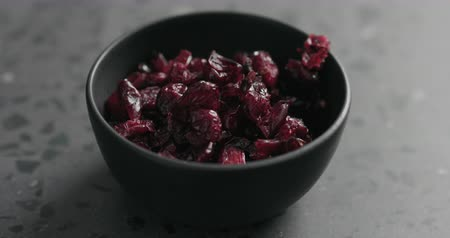 arandanos rojos : Slow motion dried cranberry falling into black bowl on terrazzo countertop