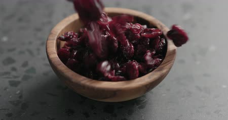 клюква : Slow motion dried cranberry falling into olive bowl on terrazzo countertop